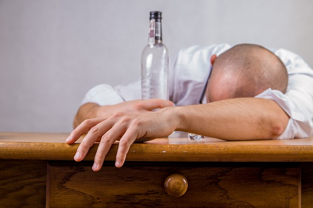 Discouraged man with an empty liquor bottle in his hand.