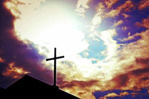 Cross atop a church facing a glorious sky.